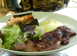 Marinated grilled turkey chops garnished with roasted eggplant, salad and  potatoes purée