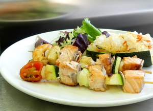 Salmon skewer with salad and courgette filled with rice and vegetables