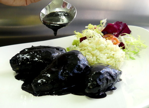 Squid stewed in their own ink with rice pilaf and salad