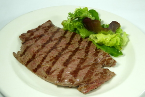 Grilled veal steak with lettuce salad