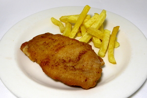 Breaded and pan fried pork loin stuffed with ham and cheese, chips
