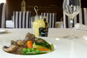Veal ragout seasoned with mustard and garnished with mixed vegetables in sticks