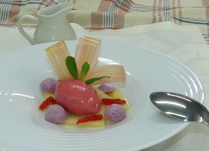 Rhubarb in its own juice garnished by strawberry-rhubarb ice cream, glazed rhubarb and caramel