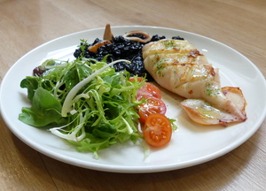 Grilled squid with black risotto and salad