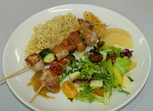 Brocheta de solomillo de cerdo con arroz integral al curry Thai y ensalada.
