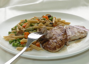 Pork tenderloin with whole grain pasta and vegetables jardiniére