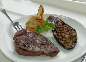 Grilled rib eye with salad, roasted aubergine and hummus